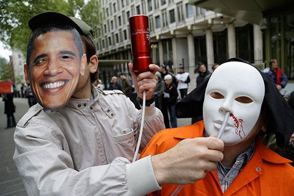 लंदन स्थित अमेरिका दूतावास के बाहर अमेरिकी राष्ट्रपति बराक ओबामा का मास्क लगाकर प्रदर्शन करता एक व्यक्ति।