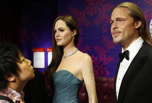 टोक्यो में मैडम तुसाद म्यूजियम में अमेरिकी अभिनेत्री एजेलिना जोली और अभिनेता ब्रेड पिट की मोम की प्रतिमा को निहारता युवक।