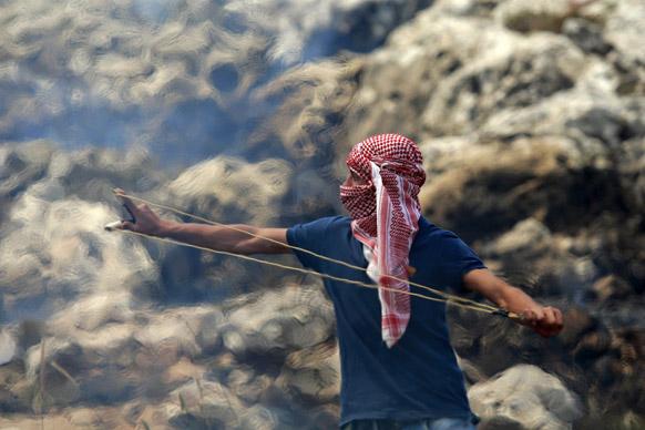 इजरायली सैनिकों के साथ टक्कर लेने के क्रम में गुलेल से पत्थर छोड़ता एक व्यक्ति।
