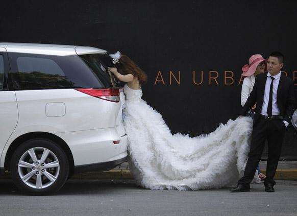 चीन में एक विवाह के दौरान दुल्हन के लंबे वेडिंग गाउन को उठाकर चलता उसका दूल्हा।