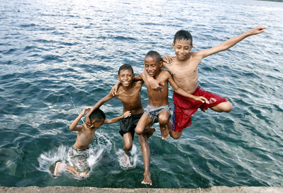 इंडोनिशिया के एक समंदर में पानी से अटखेलियां करते बच्चे।