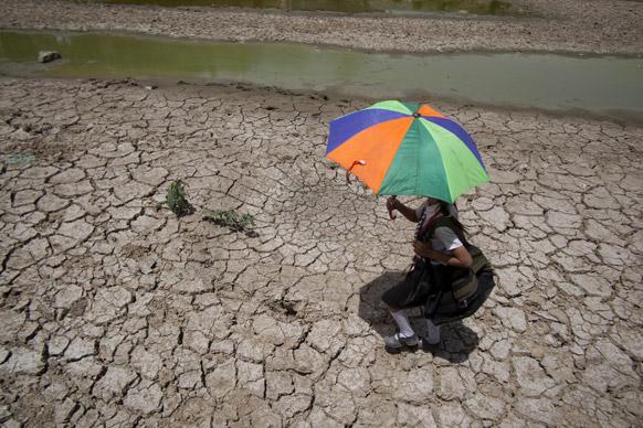 जम्मू के एक तालाब पर चढ़कर स्कूल जाती एक लड़की जिसका पानी सूख चुका है।