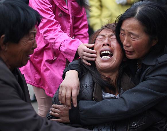 चीन में पॉल्ट्री प्रोसेसिंग वर्कशॉप में हुई आगजनी में मृतकों के परिजन विलाप करते हुए।