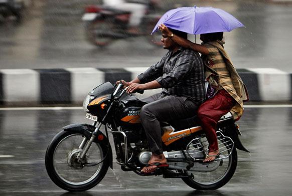 हैदराबाद में बारिश से बचने की कोशिश करता एक जोड़ा।