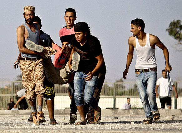 लीबिया के बेनगाजी में सरकार के खिलाफ प्रदर्शन में घायल प्रदर्शनकारी।