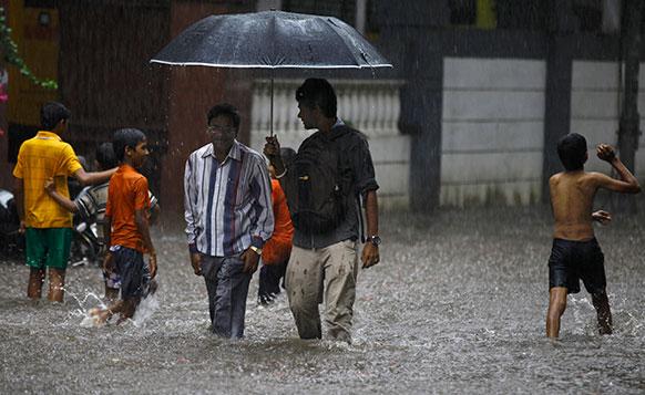 मुंबई में बारिश की वजह से गलियों में आई बाढ़ में खेलते बच्चे।