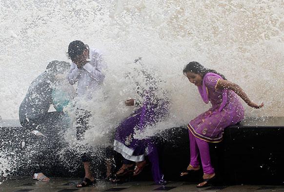 मुंबई में समंदर किनारे बारिश का मजा लेते लोग।