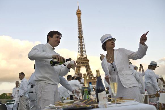 पेरिस के एफिल टावर के नजदीक व्हाइट डिनर की तैयारी में व्यस्त कुछ कलाकार।