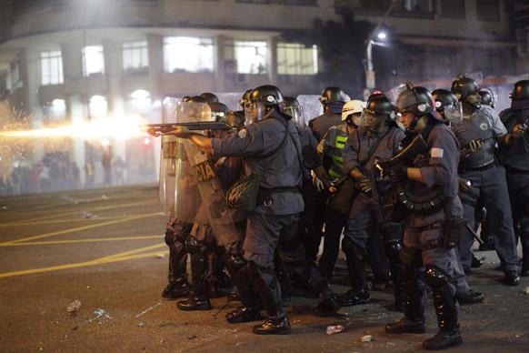 ब्राजील में प्रदर्शनकारियों पर रबर बुलेट छोड़ते पुलिसकर्मी।