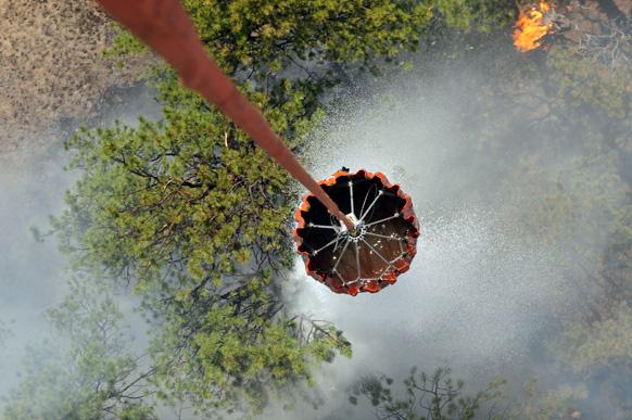 कोलो में जंगल की आग को बुझाने के लिए हेलीकॉप्टर से पानी का छिड़काव किया जा रहा है।