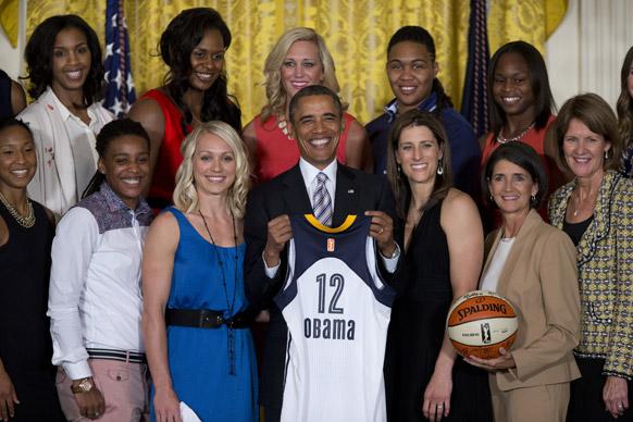 व्हाइट हाउस के पूर्वी कक्ष में इंडियाना फीवर बास्केटबॉल टीम की जर्सी को हाथ में थामे अमेरिकी राष्ट्रपति बराक ओबामा।
