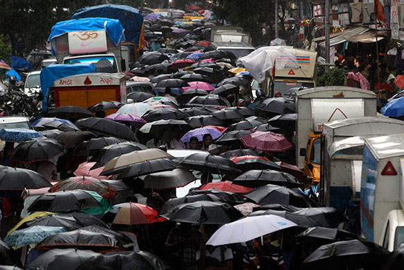 मुंबई में भारी बारिश के चलते एक रेलवे स्टेशन के बाहर लोगों का जमावड़ा।