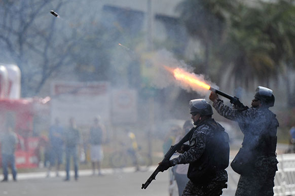 ब्राजीलिया में प्रदर्शनकारियों पर रबड़ की गोली दागता एक पुलिसकर्मी।