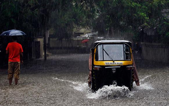 मुंबई में भारी बारिश के चलते सड़क पर जगह-जगह पानी जमा हो गया है।