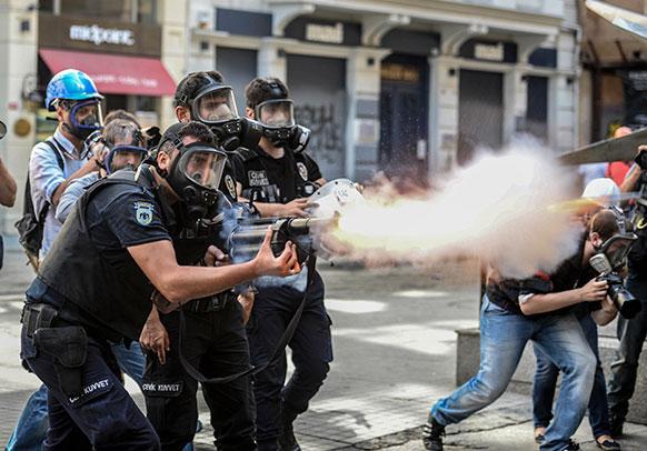 तुर्की के इंस्ताबुल में प्रदर्शनकारियों पर आंसू गैस छोड़ते पुलिसकर्मी।