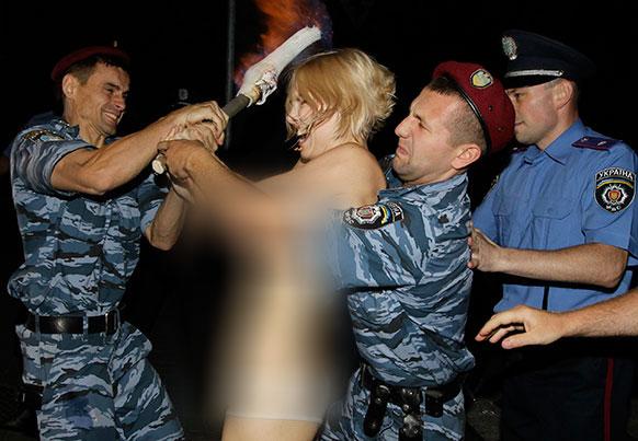 कीव में फीमेन ग्रुप की एक प्रदर्शनकारी को हिरासत में लेती पुलिस।