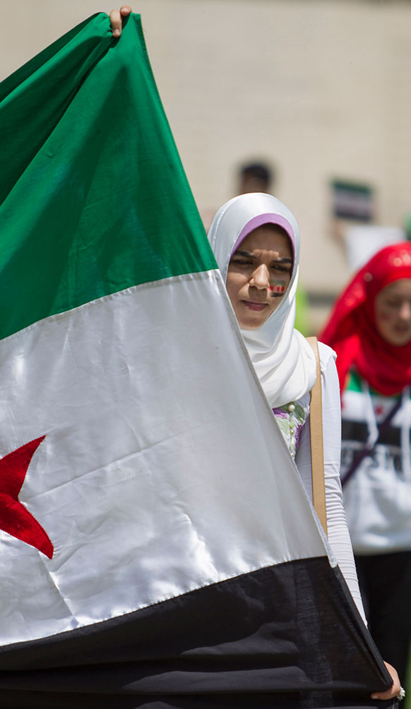 शिकागो में सीरिया के राष्ट्रपति बशर अल असद के खिलाफ प्रदर्शन करते लोग।