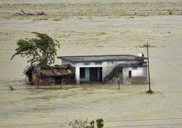 देहरादून में भारी बारिश से आई बाढ़ का एक दृश्य जहां कई घर पानी में डूब गए।