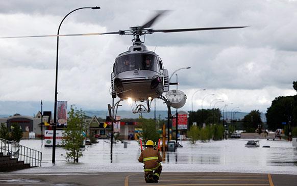 आल्डा में लोगों को सुरक्षित स्थान पर ले जाता एक हेलीकॉप्टर।
