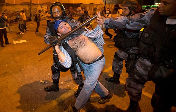 रियो डी जेनेरो में एक प्रदर्शनकारी को काबू में करती पुलिस।