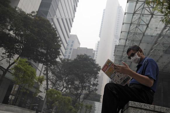 सिंगापुर में धुंध एवं कोहरे से बचने के लिए मास्क लगाकर समाचार पत्र पढ़ता एक व्यक्ति।