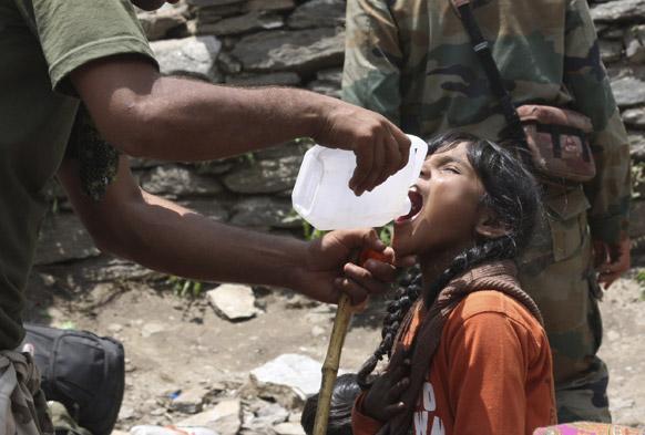 उत्तराकंड के गौरीकुंड में एक लड़की को पानी पीलाता सेना का एक जवान।