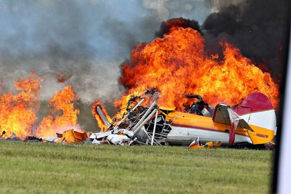 वेक्ट्रेन एयर शो के दौरान एक स्टंट प्लेन के दुर्घटनाग्रस्त हो जाने के बाद उससे उठती लपटें।