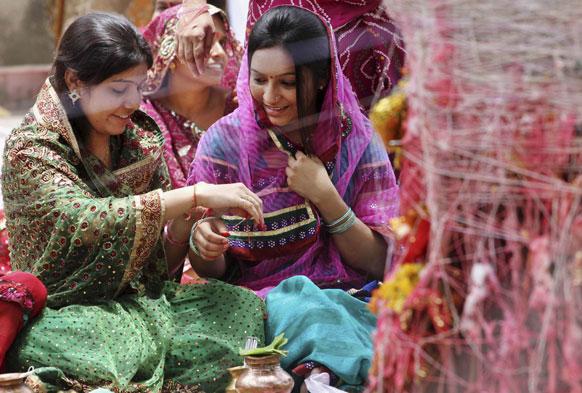 अहमदाबाद में वट सावित्री पर्व के मौके पर एक-दूसरे को पवित्र धागा बांधती महिलाएं।