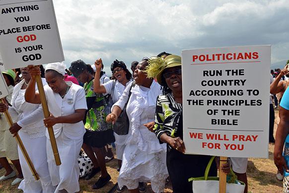 जमैका के किंग्सटन में एंटी गे रैली के दौरान लोग।