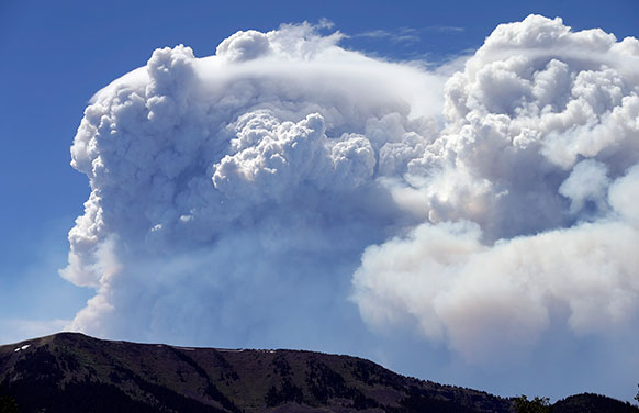 कोलो में डेल नोर्ते पीक के ऊपर फैला जंगल में लगी आग का धुआं।