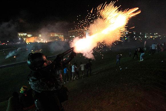 ब्राजील में प्रदर्शनकारियों पर टीयर गैस के गोली छोड़ते पुलिसकर्मी।