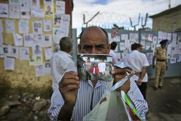जॉलीग्रांट में अपने परिवार के बिछड़े सदस्यों की तस्वीर दिखाता एक व्यक्ति।