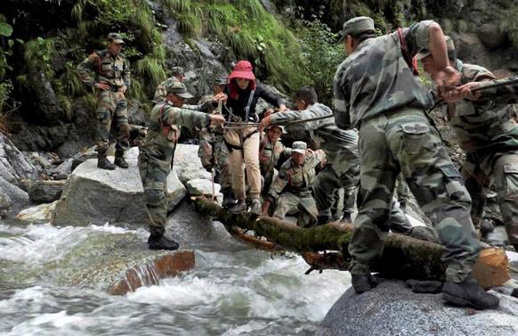पिंडारी ग्लेशियर में एक महिला को सुरक्षित निकालते सेना के जवान।