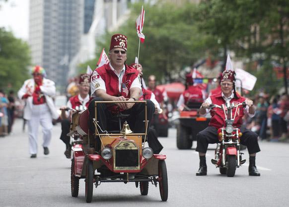 मॉन्ट्रियल में वार्षिक कनाडा डे परेड में छोटे वाहनों में साथ हिस्सा लेते लोग।