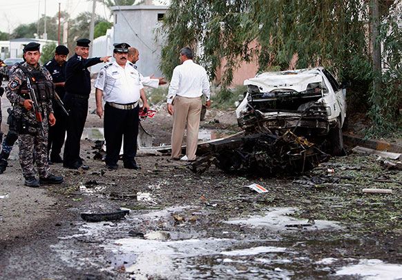 बगदाद से 550 किलोमीटर दूर बसरा में कार बम हमलों की जांच करते सुरक्षाकर्मी।