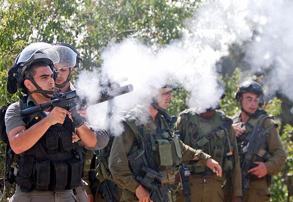 रामल्लाह में इजरायली पुलिस के लोग प्रदर्शनकारियों पर आंसू गैस छोड़ते हुए।