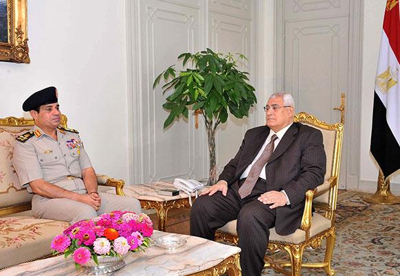 मिस्र के राष्ट्रपति भवन कार्यालय से जारी इस तस्वीर में राष्ट्रपति के महल में रक्षा मंत्री लेफ्टिनेंट जनरल अब्दुल फतह अल सिस्सी (बाएं), के साथ बैठक करते अंतरिम राष्ट्रपति अदली मंसूर।