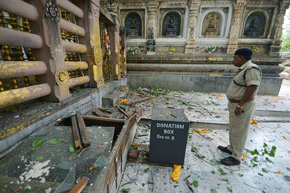 बिहार के गया में महाबोधि मंदिर के परिसर में रविवार सुबह हुए सीरियल धमाके के बाद विस्फोट स्थल का निरीक्षण करता एक सुरक्षा अधिकारी।