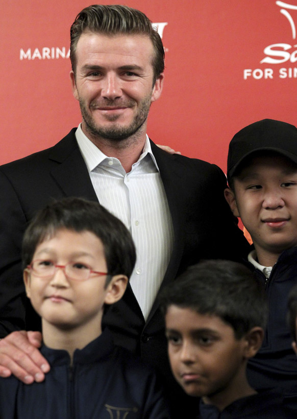 सिंगापुर के मरीना बे सैंड्स में बच्चों के साथ तस्वीर खिंचाते मशहूर फुटबॉल स्टार डेविड बेकहम।
