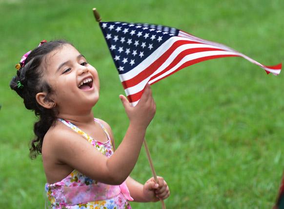 एक बच्ची अमेरिका की आजादी दिवस के मौके पर खुशी जाहिर करती हुई।  इसका परिवार एक साल पहले अमेरिका आया था।