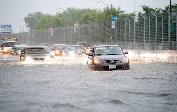 टोरंटो में आई बाढ़ में कई गाड़ियां कुछ यूं फंस गई।