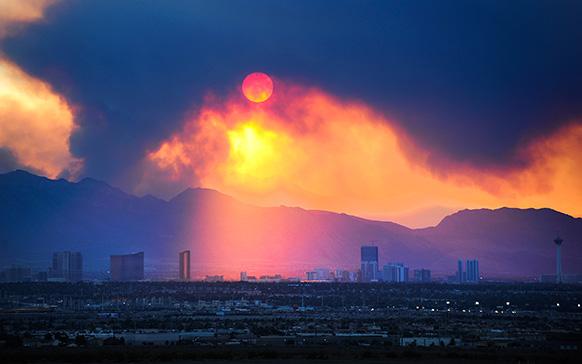 लास वेगास में सूरज के आसपास माउंट चार्ल्सटन की पहाड़ियों में लगी आग से उठा धुआं।