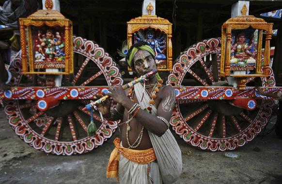 ओडिशा के पुरी में भगवान जगन्नाथ के रथ के सामने बांसुरी बजाता एक श्रद्धालु।