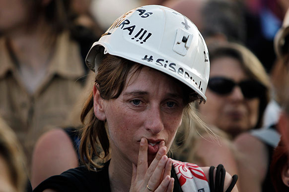 स्पेन के मैड्रिट में सब्सिडी की कटौती के खिलाफ प्रदर्शन के दौरान एक महिला।