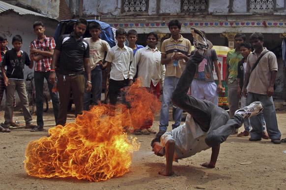 अहमदाबाद में भगवान जगनन्नाथ की रथयात्रा के दौरान आग के साथ स्टंट दिखाता युवक।