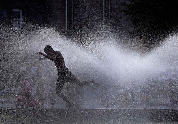 लारेंस शहर में पानी के फौव्वारों से मस्ती करते कुछ युवक।