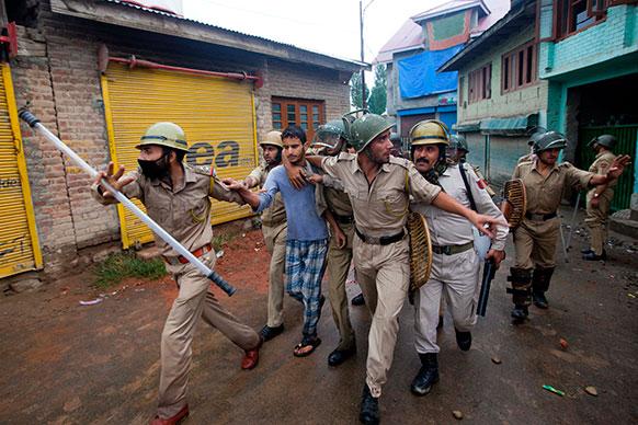 श्रीनगर में प्रदर्शनकारी को हिरासत में लेकर जाती पुलिस।