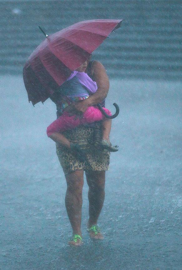निकारगुआ के मैनगुआ में बारिश से अपने बच्चे को बचाती एक महिला।