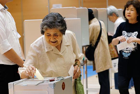जापान में उच्च सदन संसदीय चुनाव के लिए वोट डालती एक बुजुर्ग महिला।