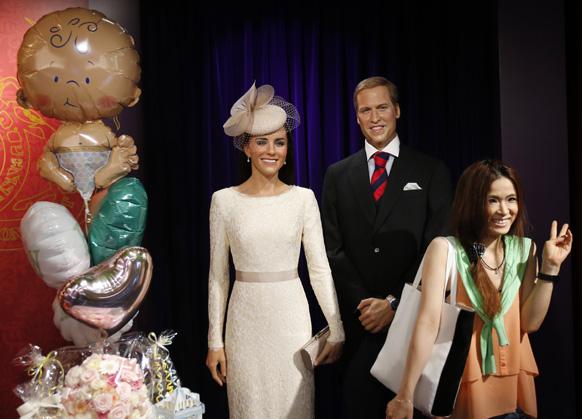 लंदन में रॉयल बेबी की जन्म की खुशी में प्रिंस विलियम और केट मिडलटन के मोम की प्रतिमा के सामने फोटो खिंचवाती हुई एक महिला।